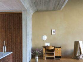 Paredes curvas de concreto atravessam a residencia do artista de